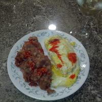 beef hash with eggs over hard and Goya hot sauce with a glass of white wine