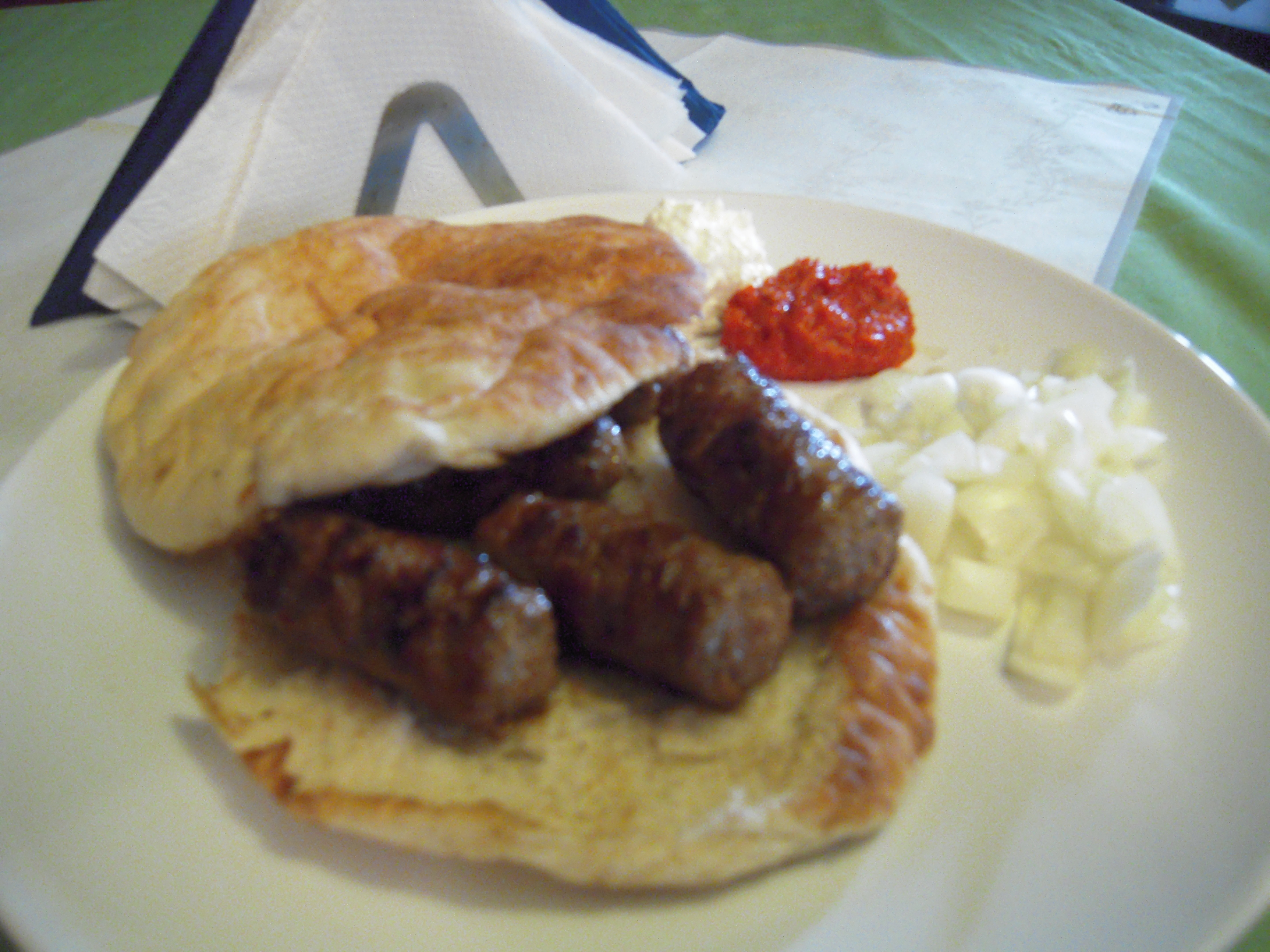 Queens, NY :: Cevapi - a Bosnian dish consisting of small  grilled beef sausages served with  lepina and chopped onion on the  side.  It's kinda awkward, because how are you supposed to eat it like a cheeseburger when the sausages will just fall out? Answer: You can't! You have to cut it up with a fork and knife..  Needless to say, it was Awesome!
