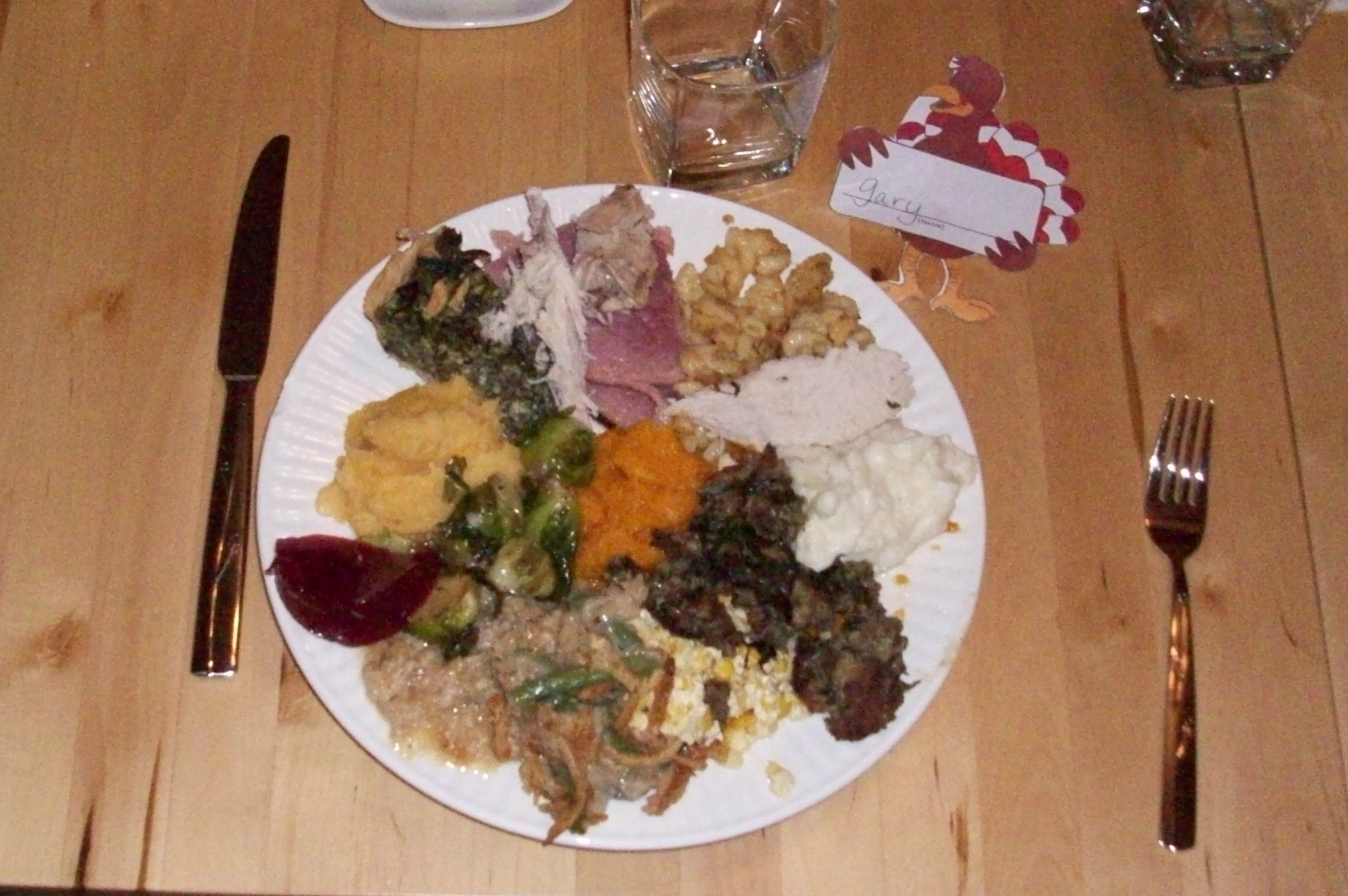 Oak Bluffs, Martha's Vinyard :: Starting at twelve o'clock with Ham, Mac n Cheese, Turkey, Mashed Potatoes Sweet Potatoes (under yje mashed), Sausage and Sage Stuffing, Corn Pudding (has a Spanish name), Green Bean casserole, Escalloped Oysters (Papa called it Oyster stuffing), Brussel Sprouts, Cranberry Sauce, Turnips, Spinach Pie, another piece of Turkey and Butternut Squash in the center.   I attempted to have a little of ev erything on my plate, however I failed, missing is Cornbread Stuffing Balls (nana calls the Svetti Balls) and Gravy.  It was all awesome.