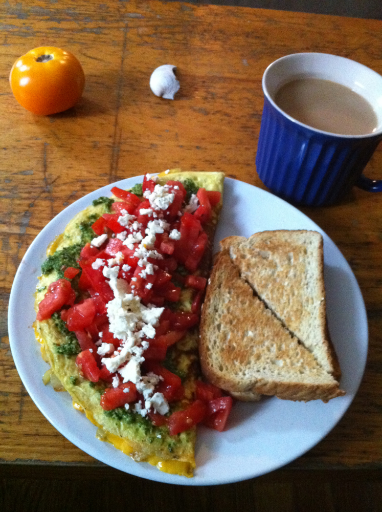 Brookline, MA :: Cage free eggs, Parker Farm tomatoes, feta, homemade pesto; red peppers, red onion, and sharp chedder in the inside. Cast iron. A dash of kosher salt and fresh ground black pepper. Freshly ground Trader Joe's peaberry coffee. Gone in a minute.