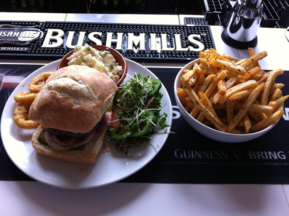 TheBoardroom, Wilmslow :: Beef burger w/ English bacon and English cheddar, mixed greens, onions rings, chips, and chefs potatoe salad. Yeah. I ate that.